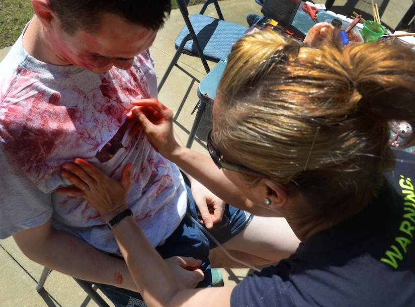 U.S. Air Force Senior Airman Peter Boyd, 628th Medical Support Squadron biomedical equipment technician, gets covered in fake blood by U.S. Air Force Master Sgt. Caroline Bunce, 628th Aerospace Medical Squadron dental hygienist, during the 2016 Lowcountry Skills Fair May 4, 2016 at Joint Base Charleston - Weapons Station, S.C. The fair was created to showcase and improve the skillset of medical professionals throughout the local area. (U.S. Air Force photo/Senior Airman Ericka Engblom)