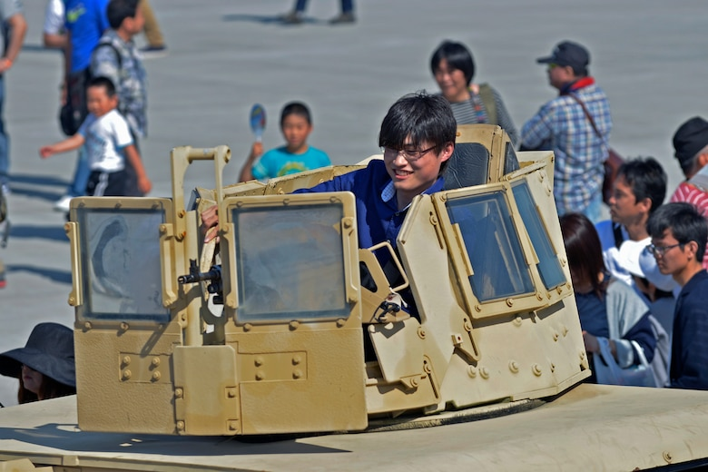 A spectator at the 2016 Friendship Day looks at a machine gun on top of a Humvee at Marine Corps Air Station Iwakuni, Japan, May 5, 2016. Approximately 175,000 guests attended the event. This year was the 40th annual Friendship Day, offering a culturally enriching experience that displays the mutual support shared between the U.S. and Japan. (U.S. Air Force photo by Senior Airman David Owsianka/Released)