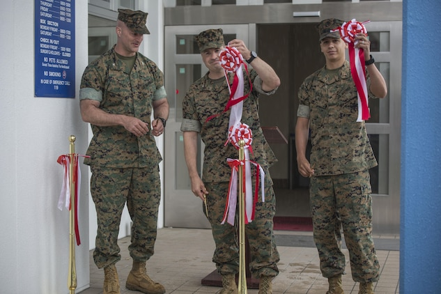 From left to right, Col. Daniel Shipley, commanding officer of Marine Aircraft Group 12, Col. Robert V. Boucher, commanding officer of Marine Corps Air Station Iwakuni, and Chief Warrant Officer Jonathan Solla, postal officer with Headquarters and Headquarters Squadron, conduct the grand opening ceremony for the new south side post office on MCAS Iwakuni, Japan, May 9, 2016. The new post office will start delivering and sending mail on opening day. (U.S. Marine Corps photo by Cpl. Nathan Wicks/Released)