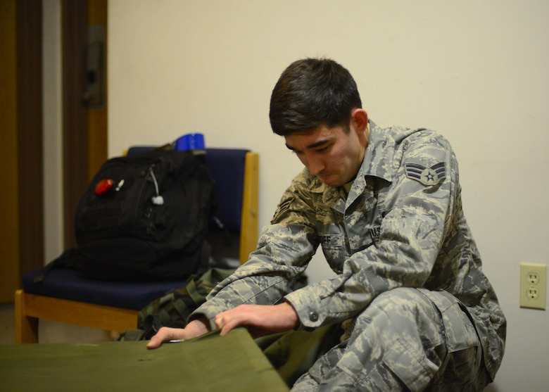 Senior Airman Maximilian Wyckoff, 51st Munitions Squadron precision guidance crew chief, secures the corner of a cot inside temporary living quarters, May 9, 2016, at Osan Air Base, Republic of Korea. Airmen from around the base temporarily relocated to buildings with built in chemical protection systems during Exercise Beverly Herd 16-01. (U.S. Air Force photo by Senior Airman Victor J. Caputo/Released)