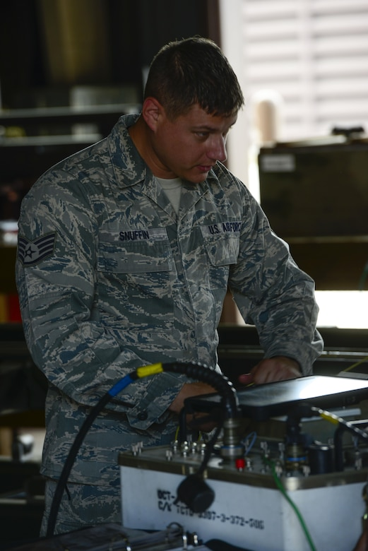 Staff Sgt. Jeffrey Snuffin, 51st Munitions Squadron conventional maintenance crew chief, reads a technical order to his crew before working on several Joint Direct Attack Munitions, May 9, 2016, at Osan Air Base, Republic of Korea. Snuffin was the lead technician in a group of Airmen updating the guidance firmware on several JDAMS as part of Exercise Beverly Herd 16-01. (U.S. Air Force photo by Senior Airman Victor J. Caputo/Released)