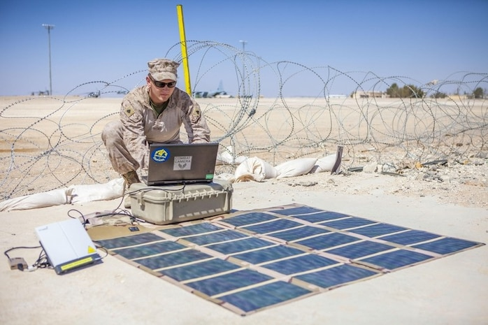 U.S. Marine Sgt. Christopher Q. Stone transmits imagery using a Broadband Global Area Network (BGAN) powered by a solar portable alternative communications energy system (SPACES) kit from King Faisal Air Base in Jordan to the USS Kearsarge at sea.