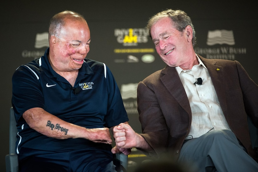 Former President George W. Bush fist bumps with Air Force Master Sgt. Israel Del Toro during the 2016 Invictus Games Symposium on Invisible Wounds in Orlando, Fla., May 8, 2016. The symposium, hosted by Bush and Britain's Prince Harry, sought to destigmatize the victims of post-traumatic stress and other injuries that are not readily visible. DoD photo by EJ Hersom
