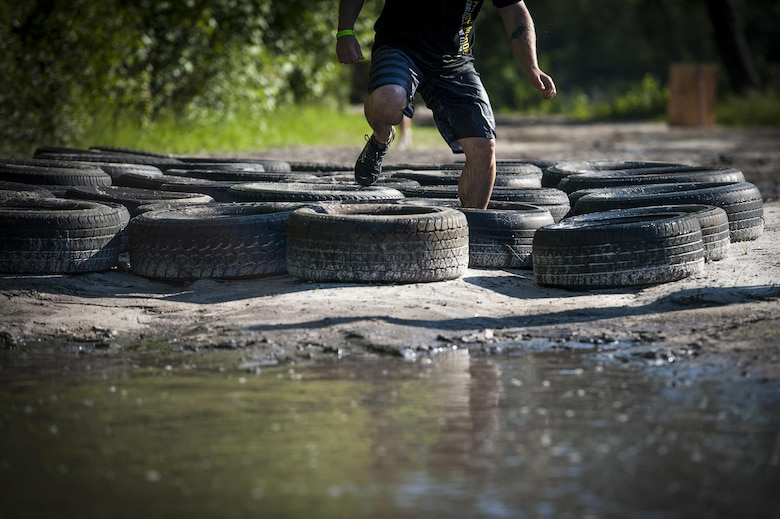 A contestant runs through tires during the 2016 Moody Mudder, May 7, 2016, in Ray City, Ga. During the race, the runners faced obstacles such as tires, monkey bars, a fire pit, and a low-crawl under barbwire. (U.S. Air Force photo by Airman 1st Class Lauren M. Hunter/Released)