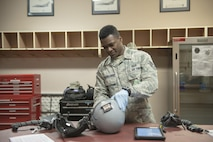 U.S. Air Force Staff Sgt. Jonathan McCullough, an 8th Operations Support Squadron aircrew flight equipment (AFE) journeyman assigned to Kunsan Air Base, Republic of Korea, inspects a flight helmet, May 2, 2016, at Eielson Air Force Base, Alaska. AFE technicians perform inspections of pilots' equipment daily to ensure it functions properly. (U.S. Air Force photo by Staff Sgt. Ashley Nicole Taylor/Released)