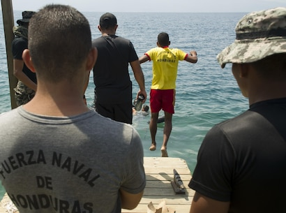 An enlisted Honduran Navy trainee jumps in the water during a swimming aptitude test April 4, 2016, on the northern coast of Honduras. The trainees took part in the first ever consolidated infantry training program in the Navy, giving them a common set of skills and knowledge to pull from in the future. (U.S. Air Force photo by Capt. Christopher Mesnard)