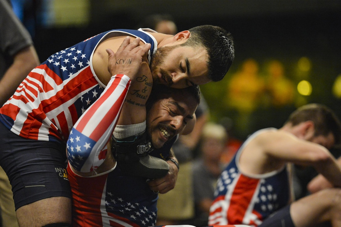 Retired Air Force Staff Sgt. Daniel Crane, left, and retired Army Staff Sgt. Michael Kacer embrace one another after competing in a rowing event during the 2016 Invictus Games in Orlando, Fla., May 9, 2016. Air Force photo by Tech. Sgt. Joshua L. DeMotts