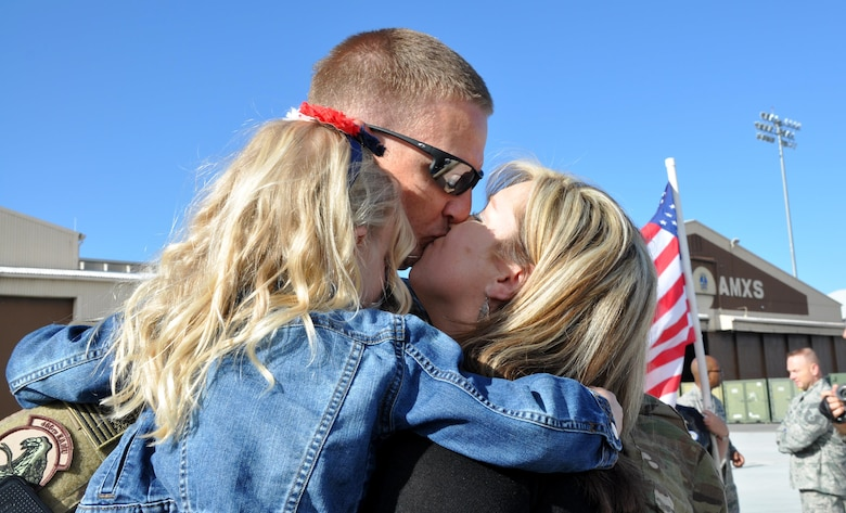 Tech. Sgt. Cliff Calhoun, a reservist in the 419th Aircraft Maintenance Squadron, embraces his wife and daughter upon returning from deployment to Afghanistan. About 300 Airmen from the active duty 388th Fighter Wing and Reserve 419th Fighter Wing returned to Hill Air Force Base on May 10. While deployed, the Airmen supported F-16 operations in the region as part of Operation Freedom's Sentinel and NATO's Resolute Support Mission. Most of the Airmen were deployed for six months. (U.S. Air Force photo/Bryan Magaña)