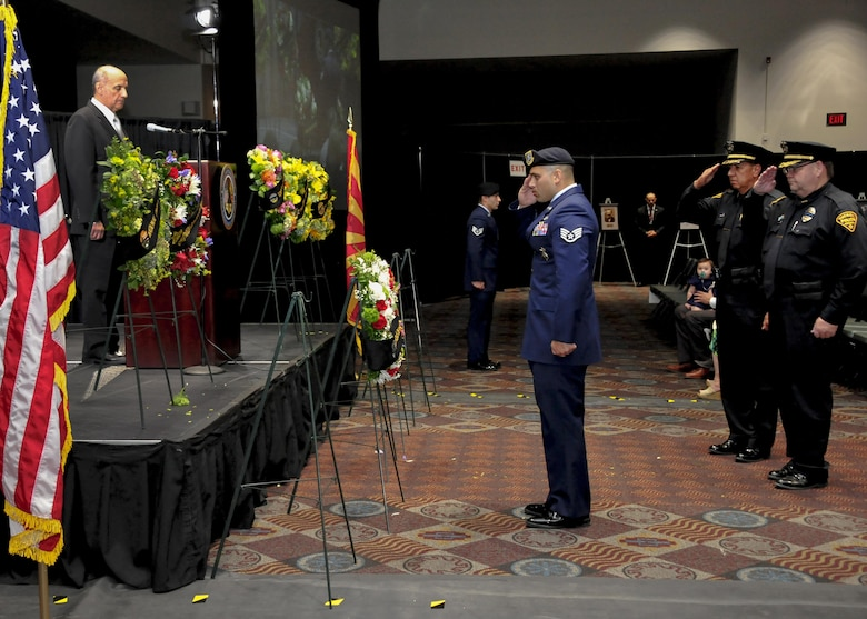 U.S. Air Force Staff Sgt. Michael Doria, 355th Security Forces Squadron member, salutes a wreath with Tucson Police Department officers during the 9th Annual Pima County Regional Law Enforcement Memorial at the Tucson Convention Center in Tucson, Ariz., May 6, 2016.  A wreath was presented by 11 local law enforcement agencies to honor past members who have perished while in the line of duty.  (U.S. Air Force photo by Senior Airman Chris Massey/Released)