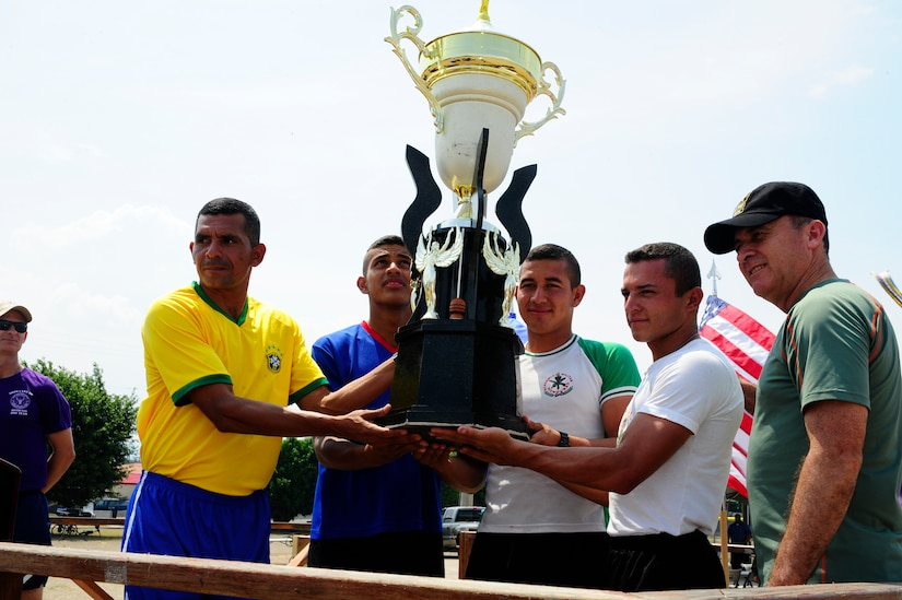 Members of the Honduran Military Training Academy hold the Camaraderie Day trophy and pose with Honduran Army Brig. Gen. Rene Ponce Fonseca, the Honduran Army Forces commander, during the 2016 Camaraderie Day closing ceremony at Soto Cano Air Base, Honduras, May 5, 2016. Following the friendly competitions, the participants ate lunch together, and by the end of the day, the athletes and attendees, through exemplary participation, promoted the spirit of friendship. (U.S. Army photo by Martin Chahin/Released)