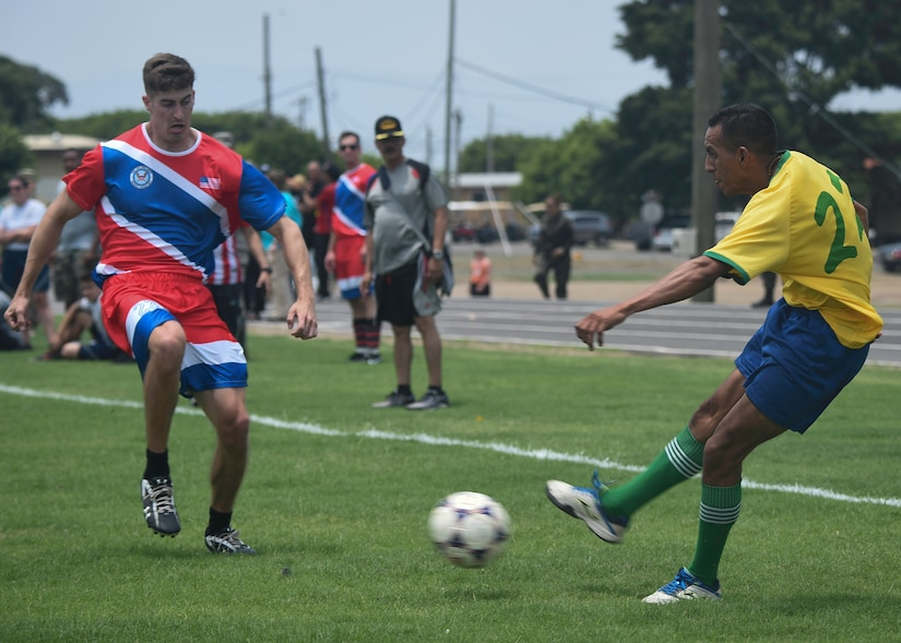 A forward on the Honduran Military Training Academy soccer team passes the ball during the 2016 Camaraderie Day at Soto Cano Air Base, Honduras, May 5, 2016. The Americans stayed stride-for-stride in the beginning of the match before falling to the Hondurans 6-1. (U.S. Air Force photo by Staff Sgt. Siuta B. Ika)