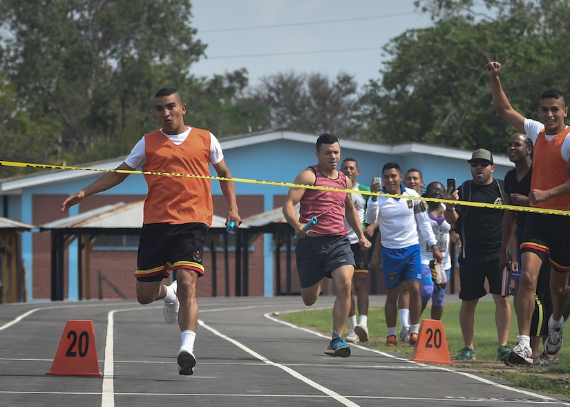 The anchor of the Honduran Military Training Academy men's 4x200 meter relay team prepares to cross the finish line ahead of the Joint Task Force-Bravo team during the 2016 Camaraderie Day at Soto Cano Air Base, Honduras, May 5, 2016. The Honduran team started off the relay with a big lead, but held on as the U.S. team rallied late. (U.S. Air Force photo by Staff Sgt. Siuta B. Ika)