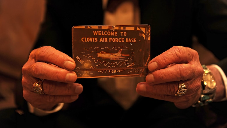 Chuck Hager, former Airman, holds a photo of himself painting the 'Welcome to Clovis Air Force Base' sign at a local coffee house April 19, 2016, in Clovis, N.M. The welcome sign, which used to be mounted at the base's main gate, was repainted by Hager in 1957 when the base was renamed as Cannon Air Force Base. (U.S. Air Force photo/Staff Sgt. Whitney Amstutz)