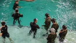 Marines with Marine Medium Tiltrotor Squadron 264 prepare to enter the helo dunker during water survival training at Marine Corps Base Camp Lejeune, Apr. 28, 2016. The Marines used a simulated helicopter body while training for different underwater escape scenarios as qualification to be attached to a Marine Expeditionary Unit.