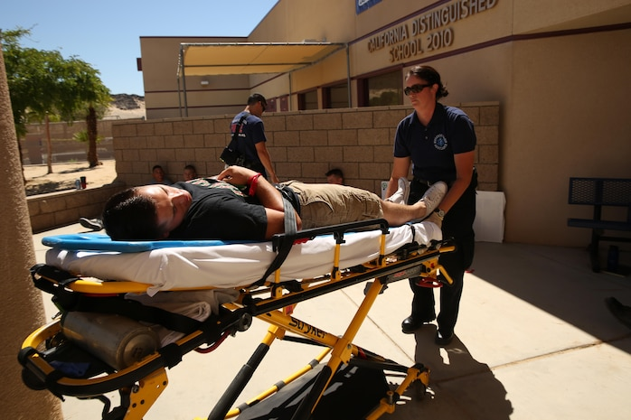 Becky Marx, a reserve emergency medical technician, transports a role player to an ambulance during an active shooter exercise at Marine Corps Air Ground Combat Center, Twentynine Palms, California. The Marine Corps is the first service to standardize E911 capabilities. The Consolidated Emergency Response Systems Program is implementing a product suite used across the nation by emergency dispatchers to locate the caller's location on a graphical display by GPS, thus increasing response time. (U.S. Marine Corps photo by Cpl. Charles Santamaria)