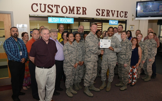 """Airman 1st Class Jourdan Coleman, 47th Force Support Squadron career development apprentice, accepts the """"XLer of the Week"""" award from Col. Thomas Shank, left, 47th FTW commander, and Chief Master Sgt. Teresa Clapper, right, 47th FTW command chief, here, May 4, 2016. The XLer is a weekly award chosen by wing leadership and is presented to those who consistently make outstanding contributions to their unit and Laughlin. (U.S. Air Force photo/Airman 1st Class Brandon May)"""
