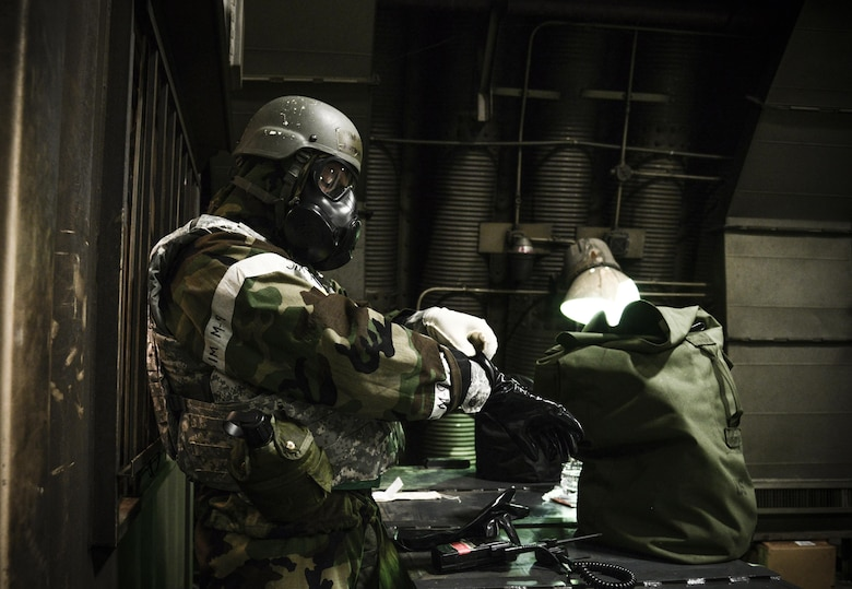 Master Sgt. Anthony Lemos, 51st Aircraft Maintenance Squadron specialist section, dons his chemical protection suit during a simulated missile attack May 10, 2016, during Exercise Beverly Herd 16-01 at Osan Air Base, Republic of Korea.  The Joint Service Lightweight Integrated Suit Technology helps protect against chemical and biological agents, radioactive fallout particles and battlefield contaminants when properly paired with the chemical protective mask. BH 16-01 is a week-long readiness exercise for the 51st Fighter Wing that includes a plethora of scenarios (U.S. Air Force photo by Tech. Sgt. Travis Edwards/Released)