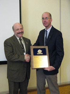 Dr. Andrew Rosenberger, right, an Air Force Research Laboratory engineer, is awarded the American Society for Testing and Materials International Award of Merit by chairman Dr. Ralph Paroli for his distinguished service and exceptional committee work in the area of metals fatigue and fracture. (U.S. Air Force photo/Steve Thompson)