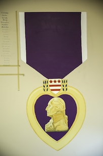 Painted on a wall inside Combat Logistics Battalion 2's headquarters building stands a 7.5-foot-tall rendition of the Purple Heart Medal, one of the most recognized and respected medals awarded to members of the U.S. armed forces. Lance Cpl. Ashley Tichensky, a motor-transportation operator with Transportation Services Company, Combat Logistics Battalion 2, spent roughly 15 hours drawing and painting a replica of the medal to represent her battalion's Marines who have been awarded this military decoration during their service. (U.S. Marine Corps photo by Cpl. Kaitlyn V. Klein/Released)