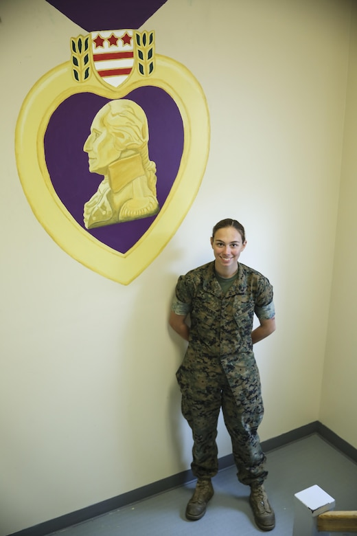 Lance Cpl. Ashley Tichensky, a motor-transportation operator with Transportation Services Company, Combat Logistics Battalion 2, poses beside her Purple Heart Medal painting at the battalion headquarters building at Camp Lejeune, N.C., May 5, 2016. In the past month, Tichensky spent roughly 15 hours drawing and painting a replica of the medal to represent her battalion's Marines who have been awarded this military decoration during their service. (U.S. Marine Corps photo by Cpl. Kaitlyn V. Klein/Released)