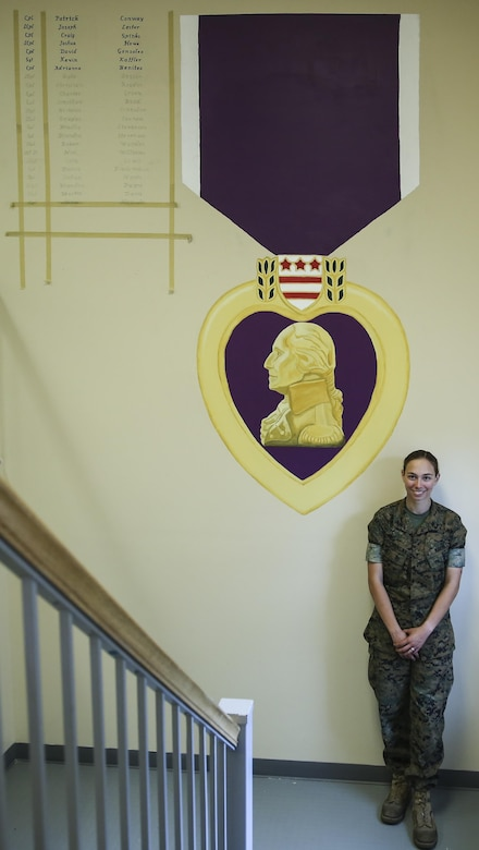 Lance Cpl. Ashley Tichensky, a motor-transportation operator with Transportation Services Company, Combat Logistics Battalion 2, poses beside her Purple Heart Medal painting at the battalion headquarters building at Camp Lejeune, N.C., May 5, 2016. During the past month, Tichensky spent roughly 15 hours drawing and painting a replica of the medal to represent her battalion's Marines who have been awarded this military decoration during their service. (U.S. Marine Corps photo by Cpl. Kaitlyn V. Klein/Released)