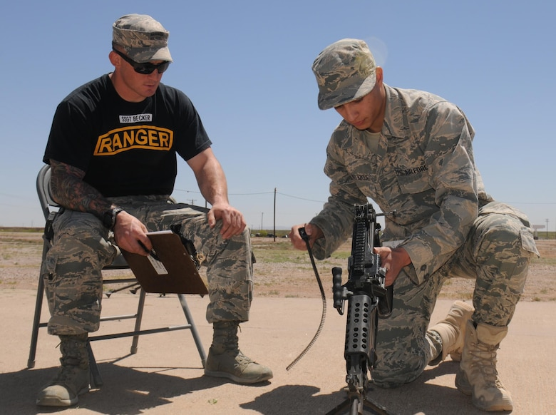 Air Force Staff Sgt. Stephen Becker, a Ranger instructor, watches Airman 1st Class Jonathan Velazquez reassemble a M249 light machine gun April 20, 2016, during an Air Force Security Forces Center Ranger assessment course at the Dona Ana Range, New Mexico. (U.S. Army photo/Staff Sgt. Corey Baltos)