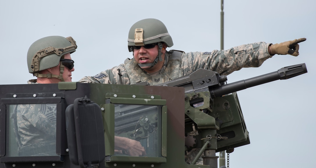 Staff Sgt. Andrew Schick, 366th Security Forces Squadron combat arms instructor, gives Chief Master Sgt. of the Air Force James Cody guidance on where to aim during target practice with a MK 19 Mod 3 May 5, 2016, at Mountain Home Air Force Base, Idaho. Cody was hitting targets approximately 1,500 meters away. The MK 19 has a maximum range of more than 2,000 meters. (U.S. Air Force photo by Airman 1st Class Chester Mientkiewicz/Released)
