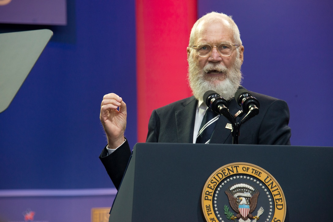 "Comedian, author, actor and former late night television host David Letterman gives remarks during a USO celebration of its 75th birthday, Military Appreciation Month and the 5th Anniversary of Joining Forces in a hangar on Joint Base Andrews May 5. The special event, called a ""Celebration of Service,"" featured special guest speakers President and First Lady Obama, Vice President and Second Lady Biden and comedic performances by Jon Stewart, David Letterman, Judd Apatow, Mike Birbiglia, Kristen Schaal, Hasan Minhaj, John Mulaney and Jeff Ross. (U.S. Air Force photo/Staff Sgt. Kat Justen)"