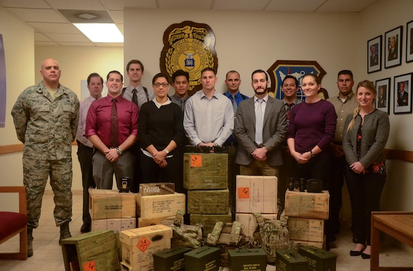 Air Force Office of Special Investigations detachment 206, stands behind ceased material after successfully completing a case during 2015 at Nellis Air Force Base, Nev. During 2015, det. 206 ran 125 cases in which they would cease stolen material, conduct busts and would receive confessions for crimes. For their actions, det. 206 was recognized as the best large Air Force OSI detachment. (Courtesy photo)