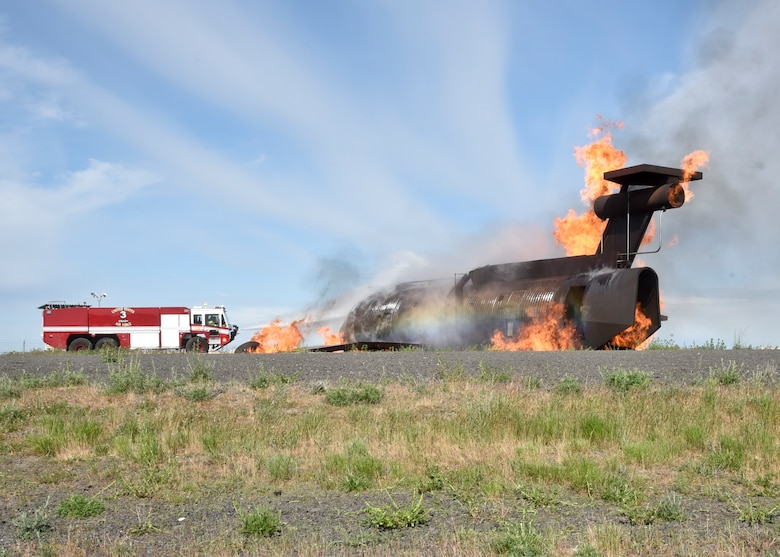 92nd Civil Engineer Squadron firefighters work to put out flames during a simulated aircraft incident May 11, 2016, at Fairchild Air Force Base, Wash. The training involved various 92nd CES agencies including members from the Fire Department, Emergency Management, Environmental and Explosive Ordinance Disposal; working together to resolve the incident. (U.S. Air Force photo/Airman 1st Class Taylor Bourgeous)