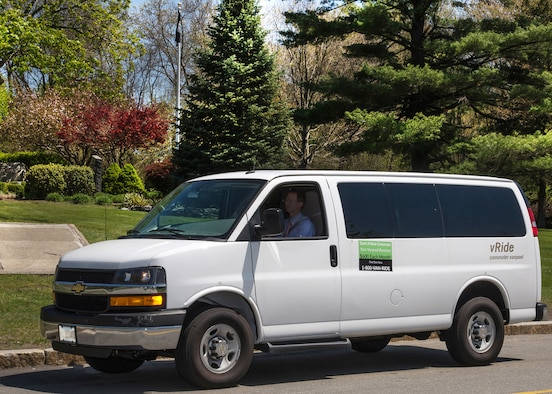 Lance Beebe drives a vRide commuting van down Grenier Street on base May 11 to pick up other riders. The United States Environmental Protection Agency recognized Scott Sheehan, an environmental engineer with the 66th Civil Engineering Division, with an environmental award for his efforts with the base's commuter program. (U.S. Air Force photo by Walter Santos)