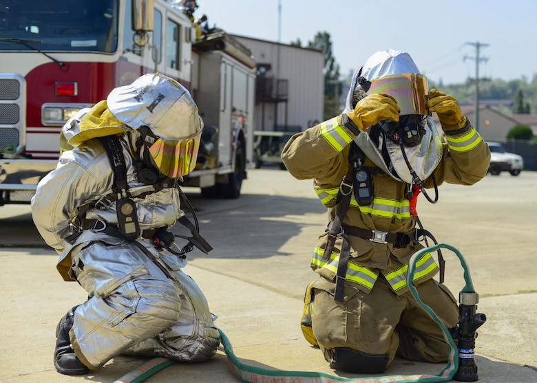 Firefighters assigned to the 51st Civil Engineer Squadron don their protective equipment before tackling a simulated vehicle fire during Exercise Beverly Herd 16-01 at Osan Air Base, Republic of Korea, May 12, 2016. The firefighters responded to the simulated fire after a mock improvised explosive device was detonated. (U.S. Air Force photo by Senior Airman Victor J. Caputo/Released)