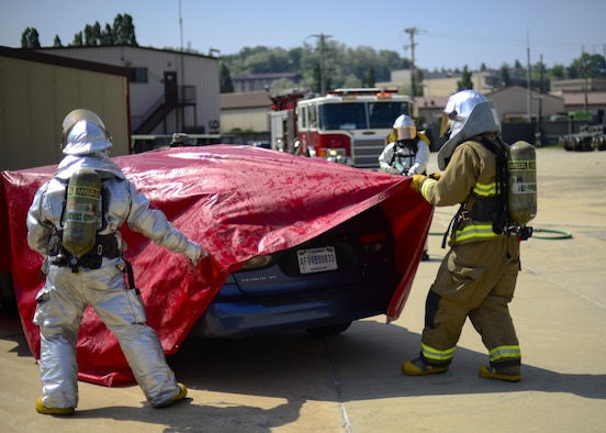 Firefighters assigned to the 51st Civil Engineer Squadron pull a tarp over a vehicle during Exercise Beverly Herd 16-01 at Osan Air Base, Republic of Korea, May 12, 2016. The vehicle was used to simulate a vehicle fire after a mock improvised explosive device was detonated, and the firefighters used the cover to help contain any possible contaminants after the fire was extinguished. (U.S. Air Force photo by Senior Airman Victor J. Caputo/Released)