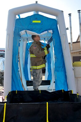 Staff Sgt. Samuel Cagle, 51st Civil Engineer Squadron firefighter, tests the portable shower on a decontamination line during Exercise Beverly Herd 16-01 at Osan Air Base, Republic of Korea, May 12, 2016. The decontamination line allows personnel leaving a hazardous area to be properly cleaned of all contaminates. (U.S. Air Force photo by Staff Sgt. Jonathan Steffen/Released)