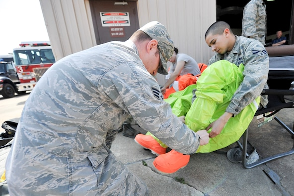 Senior Airman Mathew Ghara, 51st Civil Engineer Squadron emergency management journeyman, helps Senior Airman Mathew Castellanos, 51st CES emergency management journeyman, put on a level A HAZMAT suit during Exercise Beverly Herd 16-01 at Osan Air Base, Republic of Korea May 12, 2016. Ghara and Castellanos were responding to a mock chemical improvised explosive device to test and identify the substance. (U.S. Air Force photo by Staff Sgt. Jonathan Steffen/Released)