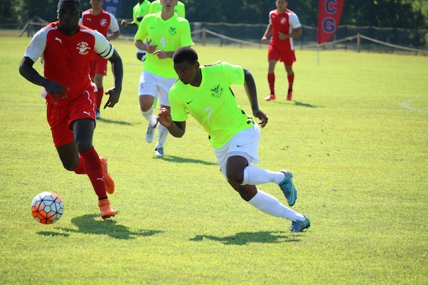 Petty Officer 2nd Class Kyle Baker (Yellow #7) drives down the field against Marine Cpl. Adrian Brown (left). Baker scored the go ahead goal lifting Navy over the Marines for the 2-1 win in match five of the 2016 Armed Forces Men's Soccer Championship hosted at Fort Benning, Ga from 6-14 May 2016.  Navy advances to the Championship Match versus Air Force.