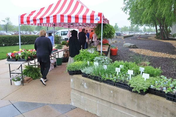 Despite the wet weather, HQC employees flock to purchase produce and plants at the kickoff of DLA's farmers' market, May 11.