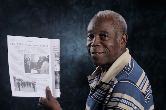 Mr. Edward Jolly, Jr, CMSgt, retired, 75, of the Air Force Intelligence, Surveillance and Reconnaissance Agency, A6, holds a Spokesman magazine showing an article depicting Jolly's 50 years of service, both military and civilian.  The AF ISR Agency/A6 Conference Room now bears his name.