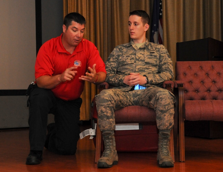 David Dittman (Left) Florida Stay Alive From Education (S.A.F.E.) Inc. presenter, explains a scenario to SrA David Van Winkle, 9th Aircraft Maintenance Squadron network management technician, at Independence Hall on Beale Air Force Base, California, May 11, 2016. Van Winkle performed as a casualty for a simulated car wreck during the Tragedy Can be Avoided event. (U.S. Air Force photo by Senior Airman Michael J. Hunsaker)