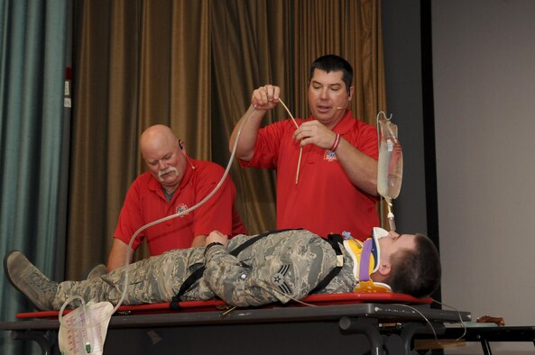 Greg McCarty (Right) and David Dittman (Top) Florida Stay Alive From Education (S.A.F.E.) Inc. presenters, perform a simulated medical examination of SrA Newton Chapman (Center) and SrA David Van Winkle (Left), 9th Aircraft Maintenance Squadron network management technicians, at Independence Hall on Beale Air Force Base, California, May 11, 2016. Chapman and Van Winkle were part of a simulated car wreck during the Tragedy Can be Avoided event. (U.S. Air Force photo by Senior Airman Michael J. Hunsaker)