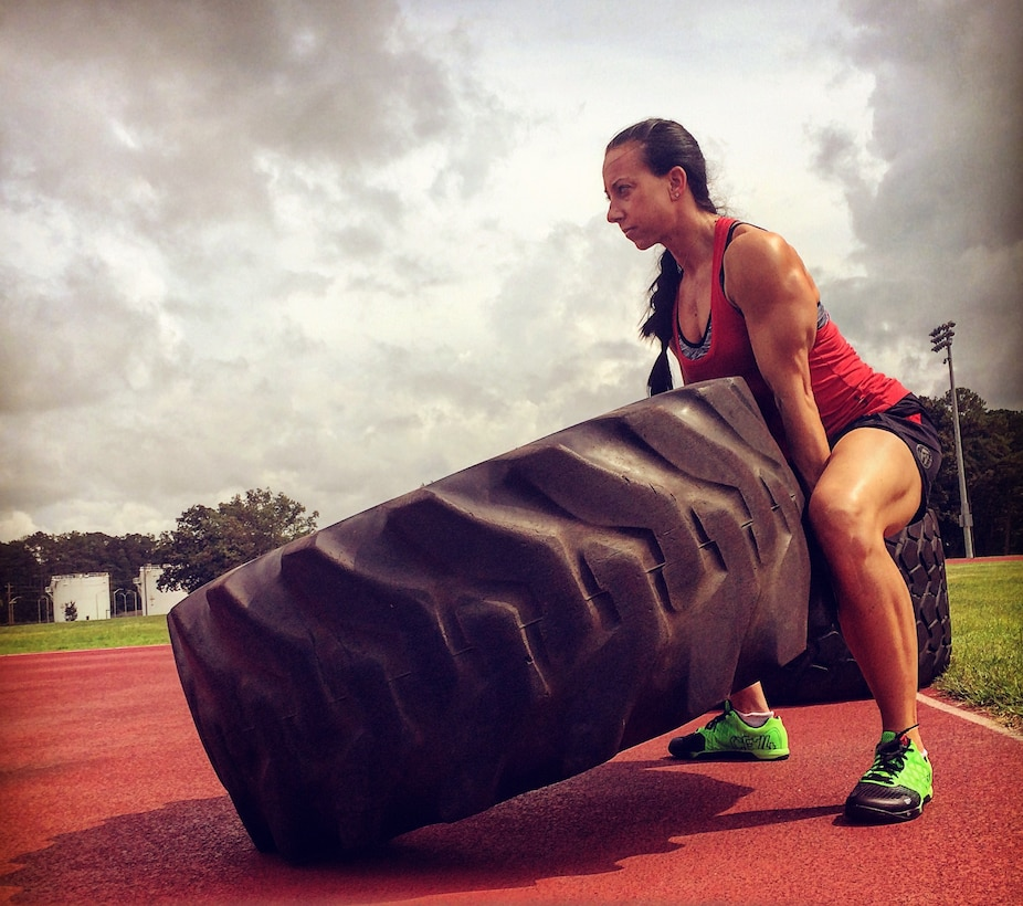 Capt. Leslie Newton, 4th Fighter Wing special victim's counselor, lifts a tire during a workout, Sept. 6, 2015, at Seymour Johnson Air Force Base, North Carolina. During her early years as a competitive athlete, Newton blew her knees four times, but even now strives to better herself at the gym. (Courtesy photo)