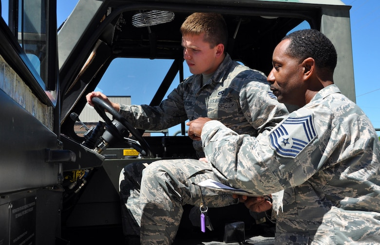 Chief Master Sgt. Lee Green, 80th Aerial Port Squadron cargo specialist, and Senior Airman Daniel Carpenter, 80th APS air transportation journeyman, review functions inside a K Loader, a series of loading truck used at Dobbins Air Reserve Base. Carpenter will be going to the Air Force Academy in July and many fellow Airmen say Carpenter has been preparing to be a pilot since he was very young. (U.S. Air Force photo by Senior Airman Lauren Douglas)
