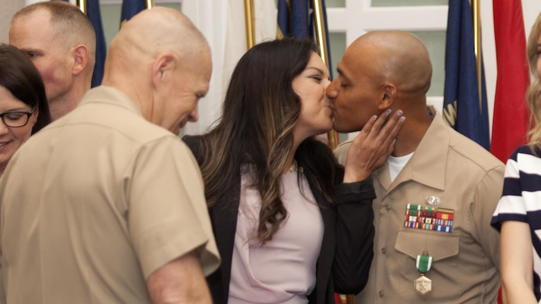 Gunnery Sgt. Miguel Cortes Jr., drill instructor of the year, kisses his wife after she is presented a certificate from the commandant of the Marine Corps at the Commandant of the Marine Corps Combined Awards Ceremony at Marine Corps Base Quantico, Virginia, May 11, 2016. The ceremony recognized top performing Marine recruiters, drill instructors, combat instructors, career planners, security guards and athletes.