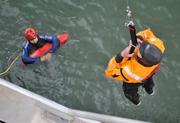 Steve Rohner, right, a crewmember of the M/V John A. B. Dillard, Jr., holds on as he is raised out of the water by a mechanized davit system May 5, while Miguel Nieto watches on. The Dillard crew conducted three days of rescue swimmer training in the San Francisco Bay May 3-5.