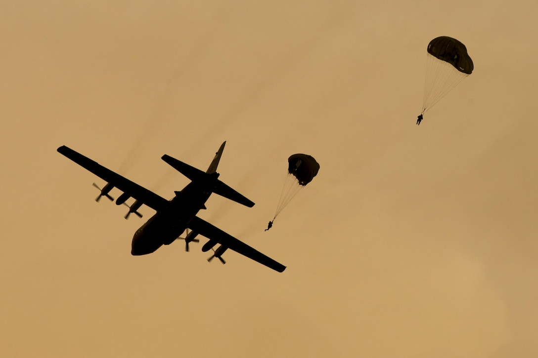 U.S. Marines from the 3rd Reconnaissance Battalion, 3rd Marine Division, III Marine Expeditionary Force drop from a U.S. Air Force C-130 Hercules, assigned to 36th Airlift Squadron at Yokota Air Base, Japan, May 11, 2016. The training not only allowed the Marines to practice jumping, but it also allowed the Yokota aircrews to practice flight tactics and timed-package drops. (U.S. Air Force photo by Yasuo Osakabe/Released)