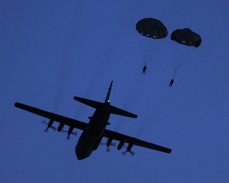 U.S. Marines from the 3rd Reconnaissance Battalion, 3rd Marine Division, III Marine Expeditionary Force drop from a U.S. Air Force C-130 Hercules, assigned to 36th Airlift Squadron at Yokota Air Base, Japan, May 11, 2016 during Jump Week. The training not only allowed the Marines to practice jumping, but it also allowed the Yokota aircrews to practice flight tactics and timed-package drops. (U.S. Air Force photo by Yasuo Osakabe/Released)