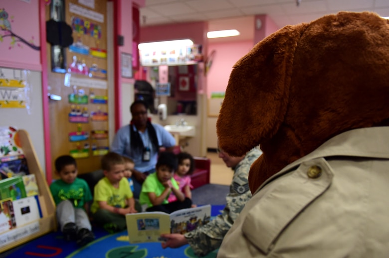 McGruff the Crime Dog listens as Buckley Air Force Base children are read to May 9, 2016, at the Crested Butte Child Development Center on Buckley AFB, Colo. McGruff, part of the National Citizens' Crime Prevention Campaign, aimed to educate adults and kids on how to stay safe. (U.S. Air Force photo by Airman 1st Class Gabrielle Spradling/Released)