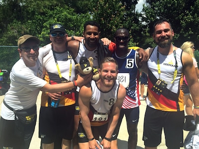 Army Reserve Staff Sgt. Zed Pitts stops for a photo with his German friend, fellow runner, 1st Sgt. Naef Adebahr and his friends after Adebahr earned his bronze medal in the men's 200-meter dash and Pitts earned his silver medal in the men's 100-meter dash in their respective disability categories during the track and field competition at the 2016 Invictus Games at the ESPN Wide World of Sports Complex, Walt Disney World, Orlando, Fla., May 10, 2016. DoD photo by Shannon Collins