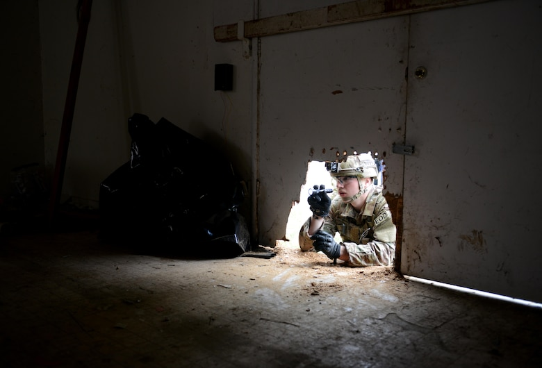 "Airman 1st Class Alex Nona, a 60th Civil Engineer Squadron explosive ordnance disposal technician, inspects the interior of an abandoned structure, known as the ""bomb factory,"" prior to entry during an exercise May 5, 2016, at Clear Lake, Calif. Nona and other EOD technicians set out to eliminate numerous improvised explosive devices and a radioactive dispersal device within the abandoned structure. (U.S. Air Force photo/Senior Airman Bobby Cummings)"