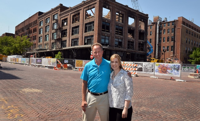 Ken Smith, a weather operations requirements manager with to the 557th Weather Wing, and Lisa Gill, with the 55th Force Support Squadron, stand in front of the Mercer Building in downtown Omaha, Neb., May 5, 2016.  The barrier fence, that surrounds the construction site, is decorated with printed banners depicting Omaha-area artists' contributions to the Old Market Business Association beautification project designed to shield the site until the restoration is completed.  (U.S. Air Force photo by Josh Plueger/Released)